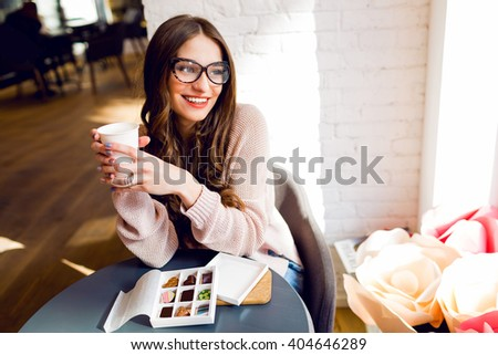 Close up  portrait of young stylish cheerful girl holding cup of coffee or tea looking with smile on street , enjoying  time lunch in modern cafe during her work break.   - stock photo
