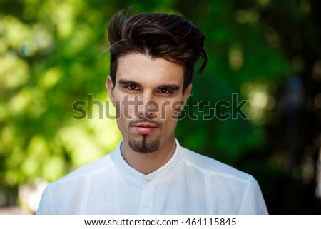 Close up portrait of young successful businessman looking at camera, walking around city.