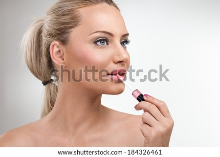 Close-up portrait of young woman applying lip gloss  - stock photo