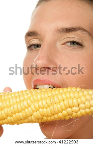 Close-up portrait of young woman biting corn-cob - stock photo