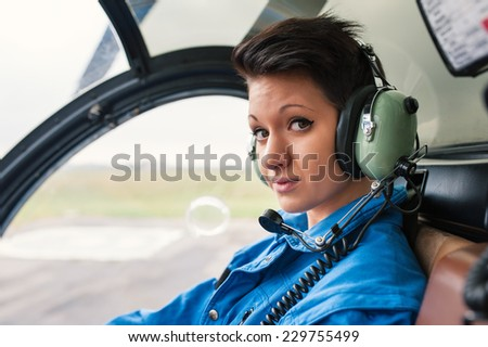 Close up portrait of young woman helicopter pilot. - stock photo