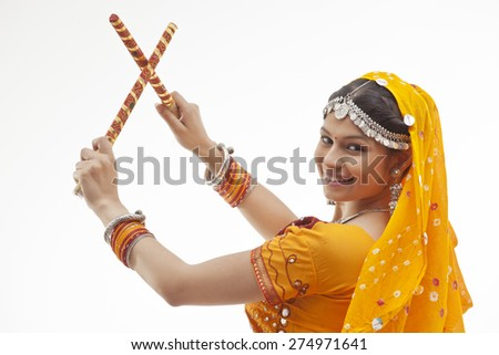 Close-up portrait of young woman holding dandiyas isolated over white background - stock photo