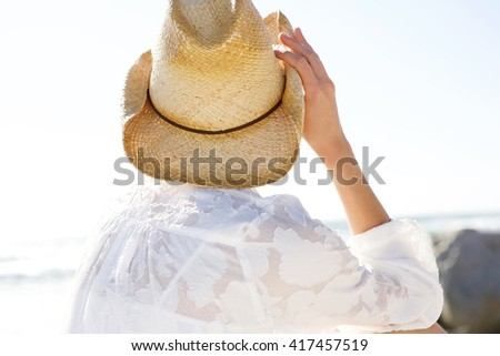 Close up portrait of young woman in hat looking at the sea from behind - stock photo