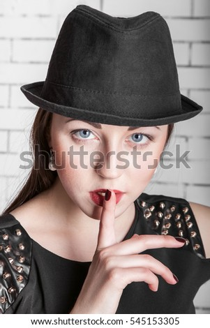 Close-up portrait of young woman in hat placing finger on lips, gestures silently, quiet, shhhhh, secret, facial expression, human emotions, signs and symbols