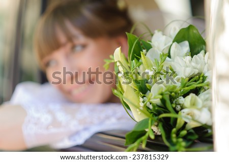 Close up portrait of young woman in wedding dress with bunch of flower. Focus on flowers, woman defocused - stock photo