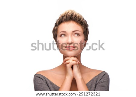 Close up portrait of young woman praying and looking up with copper-colored hair, isolated on white background - stock photo