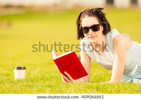 Close-up portrait of young woman reading a book and drinking coffee to go outside in the city park - stock photo