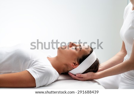 Close up portrait of young Woman relaxing with eyes closed at reiki session.Girls head resting on therapist hands. - stock photo