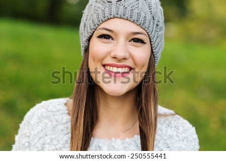 Close up portrait of young woman smiling in a park.  - stock photo