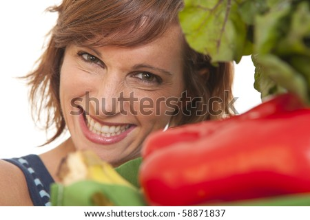 Close up portrait of young woman smiling with vegetables - stock photo