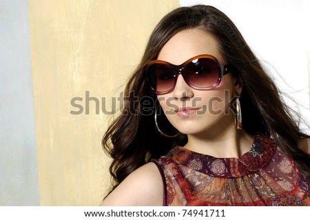 close-up portrait of young woman wearing stylish sunglasses - stock photo