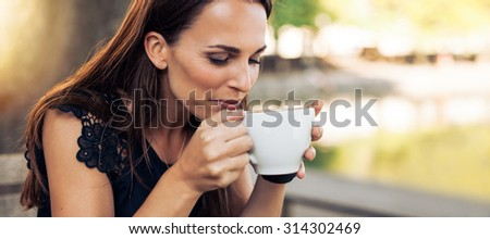 Close up portrait of young woman with an aromatic coffee in hands. Female drinking coffee at cafe. - stock photo