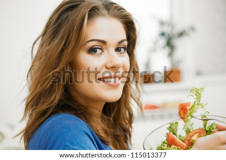 Close up portrait of young woman with long hair sitting  on sofa at home and eating healthy food.