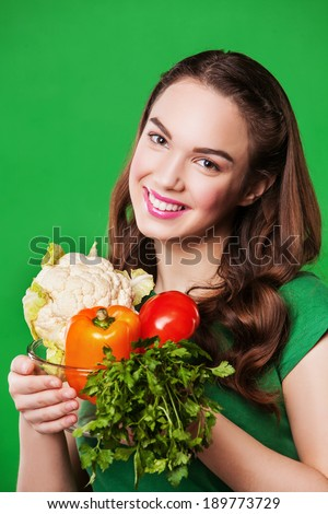 close up portrait of young woman with vegetables. on green background.