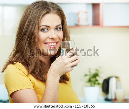 Close up portrait of Young Woman with water glass standing against  home kitchen interior. - stock photo