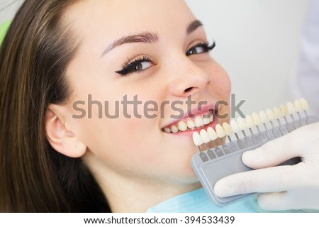 Close up portrait of Young women in dentist chair, Check and select the color of the teeth. Dentist makes the process of treatment in dental clinic office.Dentist - stock photo