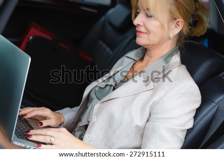 Close-up portrait old senior business woman 60-65 years ,sitting in a car, holding her Laptop Computer pc in lap and type on the keyboard - stock photo
