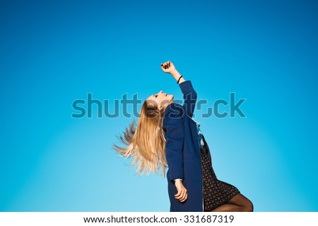 close-up portrait on a background of blue sky autumn lifestyle of young beautiful girl with stylish blonde with long hair blonde outdoors in coat and scarf  is laughing and happy - stock photo