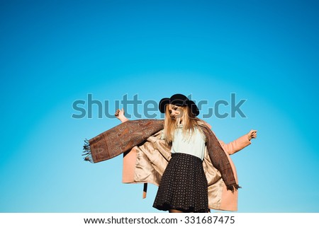 close-up portrait on a background of blue sky autumn lifestyle of young beautiful girl with stylish blonde with long hair blonde outdoors in coat and scarf and hat is laughing and happy - stock photo