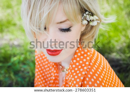 close-up portrait outdoors young beautiful girl in an orange hipster blonde bright cheerful polka dot blouse , smiling red plump lips on the background of green grass - stock photo