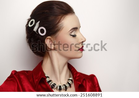 Close up portrait perfect woman face profile. Stylish hair dress, bobby pin, silver expensive jewelry necklace, red blouse shoulders, white background, red lips, make up, closed eyes, thinking dream  - stock photo