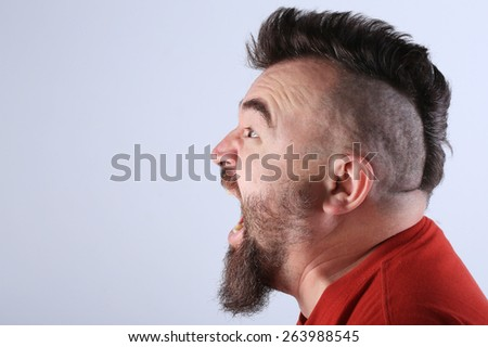 close-up portrait profile of a white man with mohawk and beard screams in a angry state - stock photo
