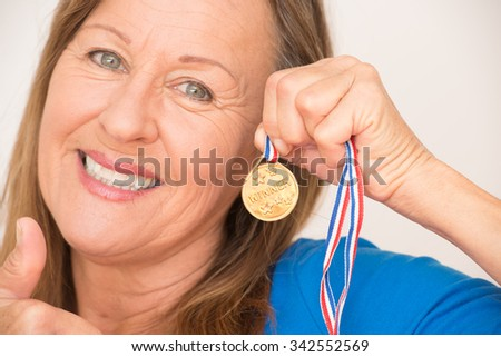 Close Up Portrait proud active attractive mature woman presenting confident happy smiling and positive thumb up her winning gold medal award. - stock photo
