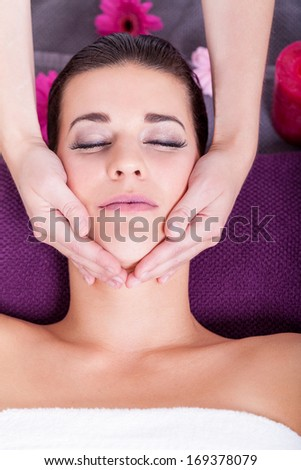 Close-up portrait shot from above of a young attractive brunette woman having a relaxing facial massage, in a fancy spa center, with scented candles and flowers - stock photo