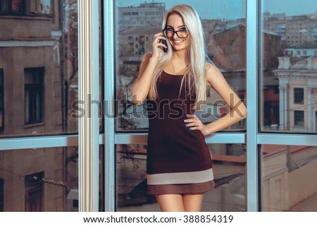 Close up portrait smiling blonde woman talking phone near the large window with city views. Business woman talking phone. City views behind the window in the office. Business concept. - stock photo