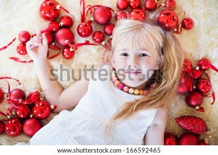 close-up portrait smiling girl lies on the fur around her rad Christmas balls   - stock photo