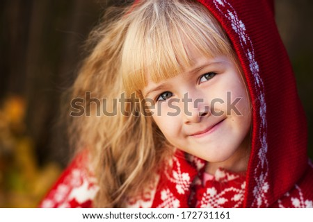 close up portrait smiling little girl in red knit poncho with hood
