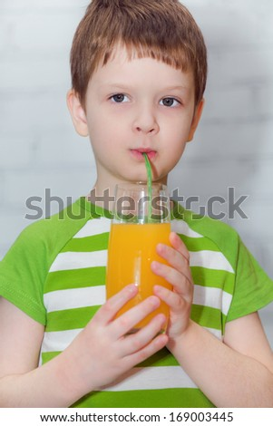 Close up portrait the child drinking orange juice out of the tube,  image on a light background.