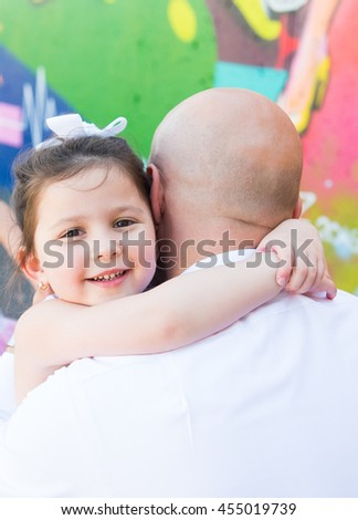 Close up portrait to beautiful cute little toddler girl hugging father