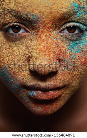 Close up portrait view of a black african american girl face with different color cosmetics powder splashes on her skin with texture and detail.
