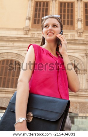 Close up portrait view of a young professional business woman holding and using a modern smartphone mobile phone to make a call holding a briefcase in a city street. Technology outdoors. - stock photo