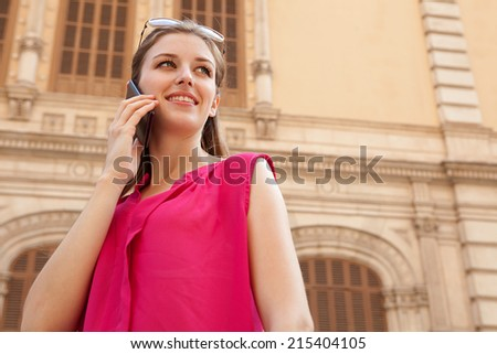 Close up portrait view of a young professional business woman holding and using a modern smartphone mobile phone to make a call while standing in a city street. Using technology outdoors. - stock photo