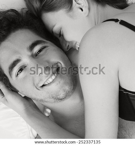 Close up portrait view of an attractive young couple sleeping together, hugging on a white linen hotel bed, indoors. Couple and romance living lifestyle. Sensuality and relationships, home interior. - stock photo