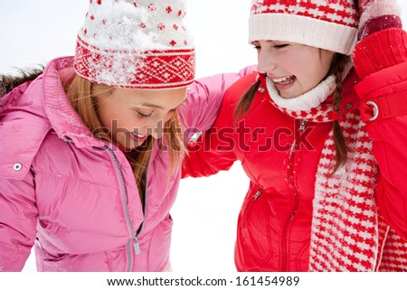 Close up portrait view of two joyful young women friends having fun and laughing while in a skiing holiday in a white snow  landspace lake with big joy expressions and excitement, outdoors. - stock photo