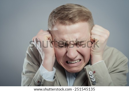 Close Up portrait young angry and unhappy stressed man covering his ears , isolated grey background. Negative emotion, face expression
