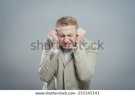 Close Up portrait young angry and unhappy stressed man covering his ears , isolated grey background. Negative emotion, face expression - stock photo