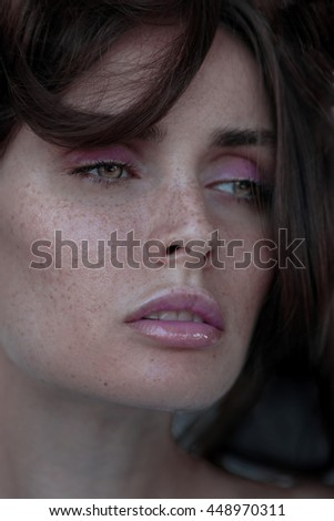 Close up portrait young beautiful girl with freckles and green eyes