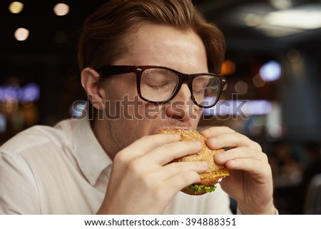 Close up portrait young man in glasses eating traditional burger in bar - stock photo
