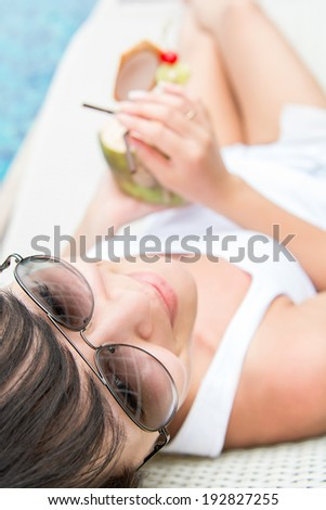 Close-up portrait young pretty woman drinking coconut cocktail  - stock photo