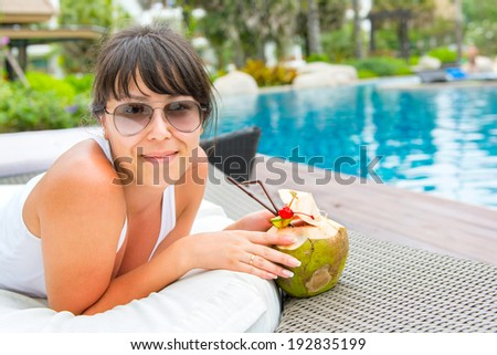 Close-up portrait young pretty woman drinking coconut cocktail against outdoor pool. Side view . Concept photo recreation and tourism - stock photo