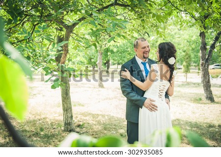 close-up portraits of the newlyweds on the background of summer green trees
