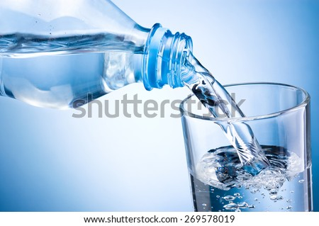 Close-up pouring water from bottle into glass on blue background - stock photo