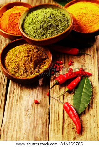 Close up Powdered Spices on Round Containers with Red Cayenne Pepper on a Rustic Wooden Table