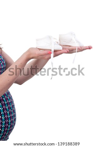 Close up pregnant woman holding pair of white shoes for baby, copy space