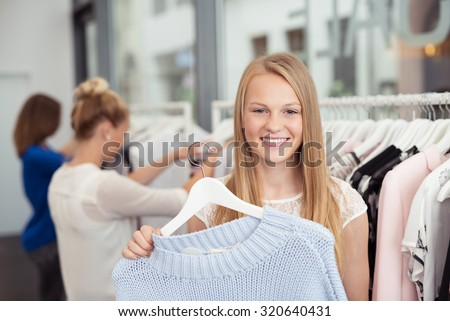 Close up Pretty Blond Girl Holding a Hanged Shirt Inside a Clothing Store and Smiling at the Camera - stock photo