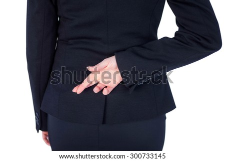 Close up pretty businesswoman with finger crossed against a white wall - stock photo